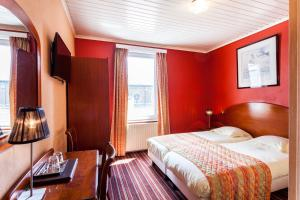 A bed or beds in a room at Malecot Boutique Hotel