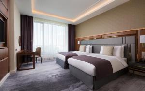Ein Bett oder Betten in einem Zimmer der Unterkunft Lotte Hotel Samara