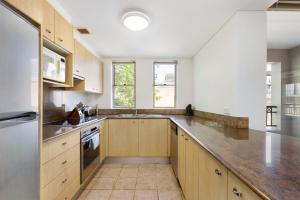 A kitchen or kitchenette at Woolloomooloo Modern Apartment 12BRK