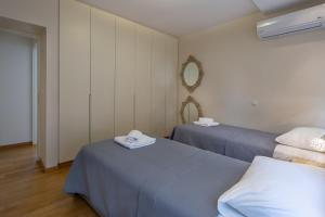 A bed or beds in a room at SAGITTARIUS - FALIRO SEA SIDE APARTMENT
