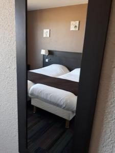A bed or beds in a room at Hôtel Sanotel