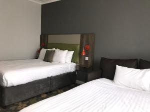 A bed or beds in a room at Epping Forest Hotel
