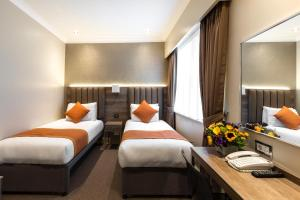 A bed or beds in a room at Sidney Hotel London-Victoria