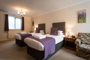 A bed or beds in a room at Blakeney Manor Hotel