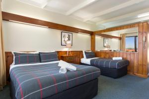 A bed or beds in a room at Village Family Motor Inn