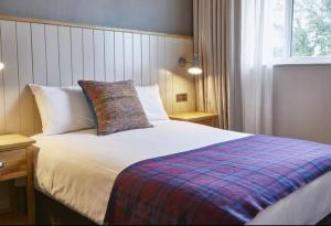 A bed or beds in a room at Feathers Inn by Greene King Inns