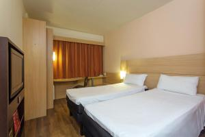 A bed or beds in a room at Ibis Salvador Rio Vermelho