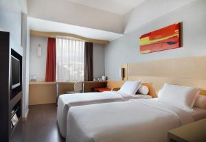 A bed or beds in a room at Ibis Jakarta Arcadia