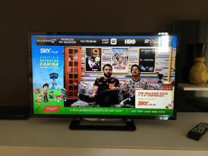 Uma TV ou centro de entretenimento em Flat Flor Que Ri