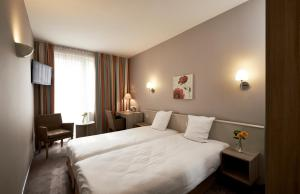 A bed or beds in a room at Leopold Hotel Brussels EU