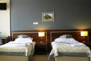 En eller flere senge i et værelse på Hotel Dębowiec