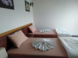 A bed or beds in a room at Dara Nopparat Hotel
