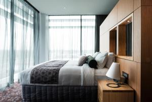A bed or beds in a room at Mercure Sydney Liverpool
