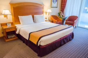 A bed or beds in a room at Avenue Hotel Dubai