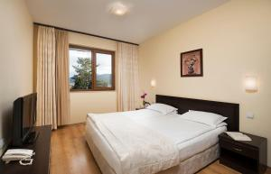 A bed or beds in a room at SPA Club Bor Hotel