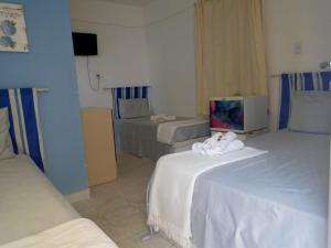 A bed or beds in a room at Pousada Asa Branca
