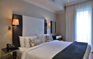 A bed or beds in a room at Cape Royale Luxury Suites