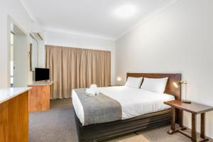 A bed or beds in a room at Rockhampton Riverside Central Hotel