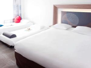 A bed or beds in a room at Novotel Lille Aéroport