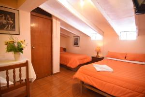 A bed or beds in a room at Tambo Cusco Inn