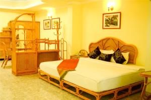 A bed or beds in a room at Evergreen Hotel
