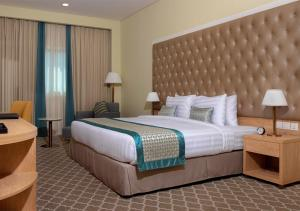 A bed or beds in a room at Jacob's Garden Hotel