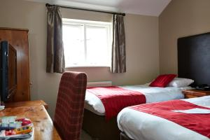 A bed or beds in a room at Bull Hotel by Greene King Inns