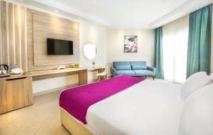 سرير أو أسرّة في غرفة في Otium Pyramisa Beach Resort Sahl Hasheesh