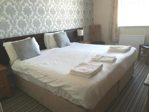 A bed or beds in a room at Pentire Hotel