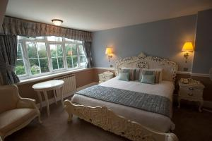 A bed or beds in a room at Manor Of Groves Hotel
