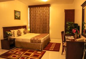 A bed or beds in a room at Al Maha Regency Hotel Suites