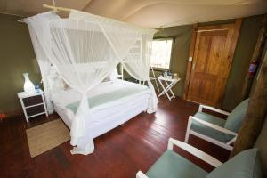 A bed or beds in a room at Ngama Tented Safari Lodge