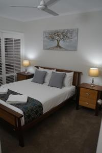 A bed or beds in a room at Airlie Seaview Apartments