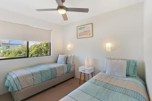 A bed or beds in a room at Low Tide on Noosa Sound - Pet Friendly