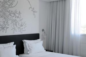 A bed or beds in a room at Open Village Sports Hotel & Spa Club