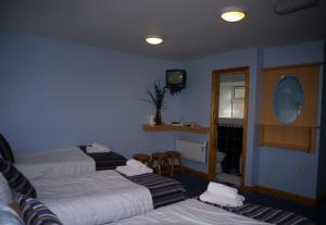 A bed or beds in a room at The Dingle Pub B&B