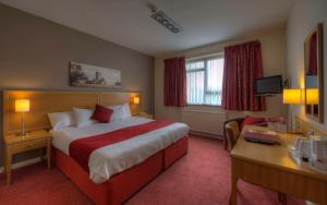 A bed or beds in a room at Kingstown Hotel by Greene King Inns