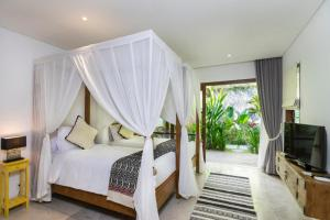 A bed or beds in a room at Calma Ubud Suite & Villas