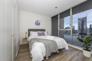 A bed or beds in a room at Canvas Suites on La Trobe