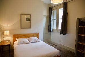A bed or beds in a room at Appartements de l'Hotel de Girard