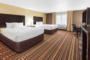 A bed or beds in a room at Days Inn & Suites by Wyndham Davenport East