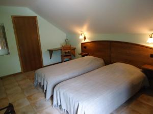 A bed or beds in a room at Hotel La Crémaillère