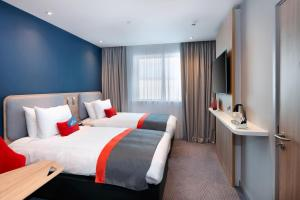 A bed or beds in a room at Holiday Inn Express - London Heathrow T4