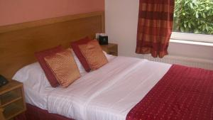 A bed or beds in a room at Woodlands Hotel