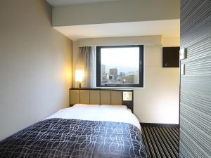 A bed or beds in a room at APA Hotel Kanda Jimbocho Ekihigashi