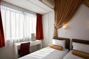 Кровать или кровати в номере Metropolis Hotel