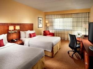 A bed or beds in a room at Courtyard by Marriott Atlanta Executive Park/Emory