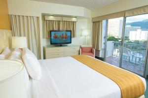 A bed or beds in a room at Coconut Waikiki Hotel