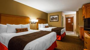 A bed or beds in a room at Best Western Plus Olympic Inn