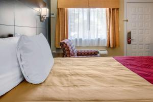 A bed or beds in a room at Econo Lodge Freeport - Brunswick Area